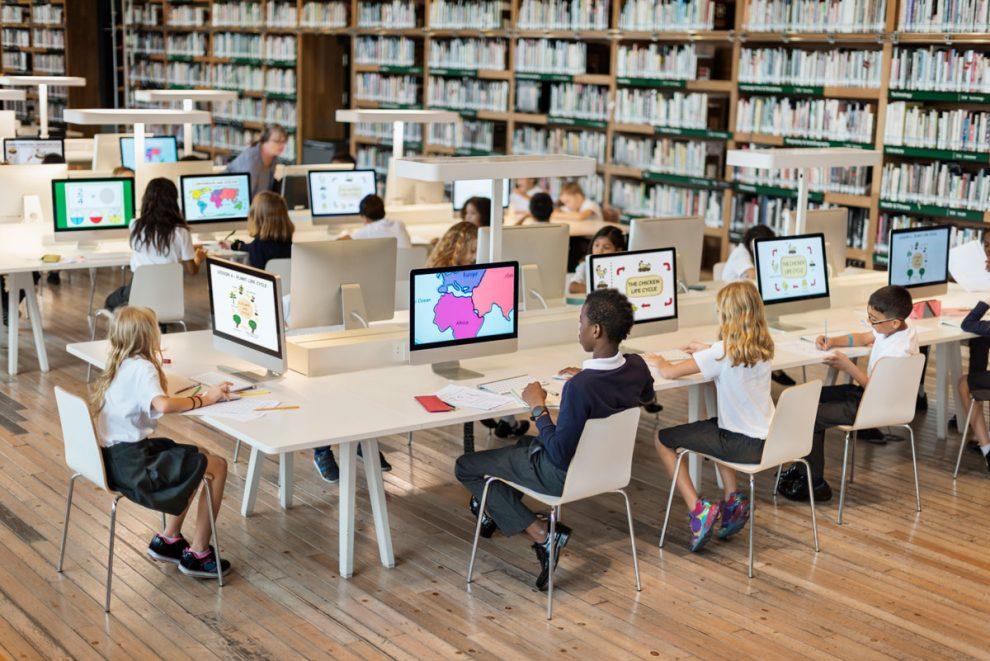 Alumnos conectados con ordenadores en biblioteca de colegio